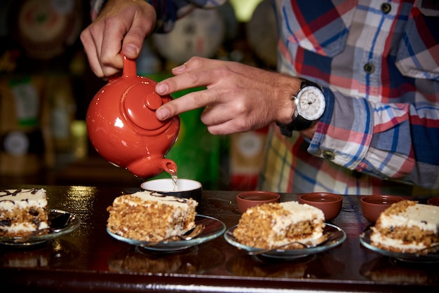 Tea ceremony. a young man pours tea in cups.