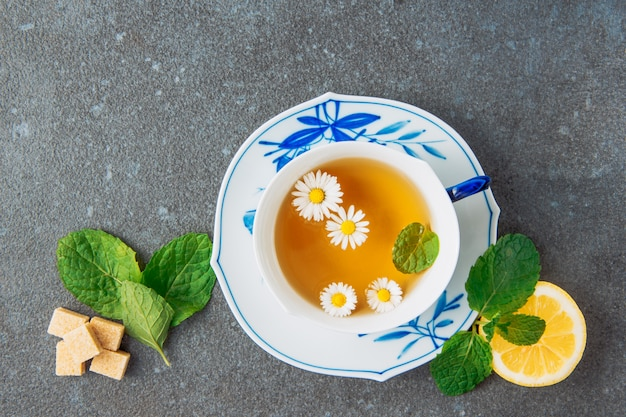 Tea of chamomile in a cup and saucer with lemon, brown sugar cubes and green leaves top view on a grey stucco background