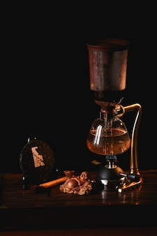 Tea composition. puer tea in the siphon with buddha statue on black background
