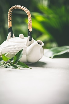 Tea composition on tropical leaves background, close up