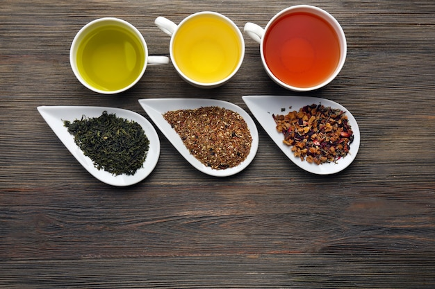 Tea concept. different kinds of dry tea in ceramic bowls and cups of aromatic tea on wooden