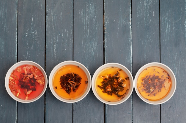 Tea concept. different kinds of dry tea in ceramic bowls and cups of aromatic tea