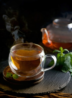 Tea concept, teapot with tea surrounded on wood surface, tea ceremony, green tea in a transparent cup