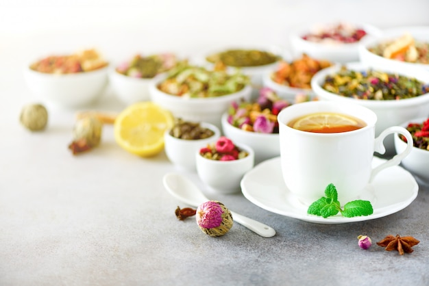 Tea concept with copy space. different kinds of dry tea in white ceramic bowls and cup of aromatic tea on grey background.