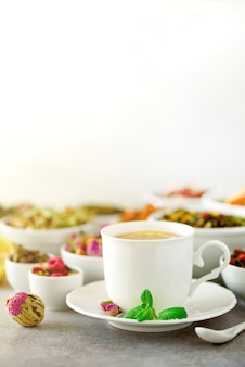 Tea concept with copy space. different kinds of dry tea in white ceramic bowls and cup of aromatic tea