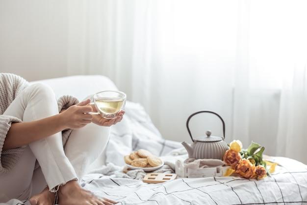 ベッドのコピースペースにお茶、クッキー、新鮮なチューリップの花束