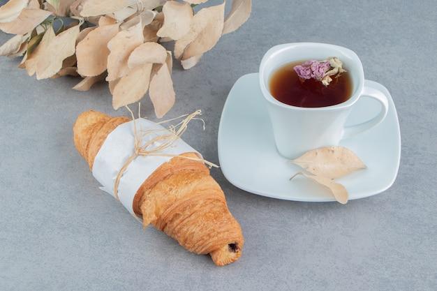 Чай, круассаны и листья на мраморном фоне. фото высокого качества