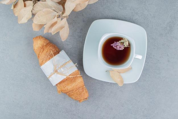 大理石の背景にお茶、クロワッサン、葉。高品質の写真