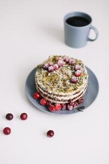 Чашка чая и домашний пирог со шпинатом и сливками, украшенный свежей клюквой на белом столе