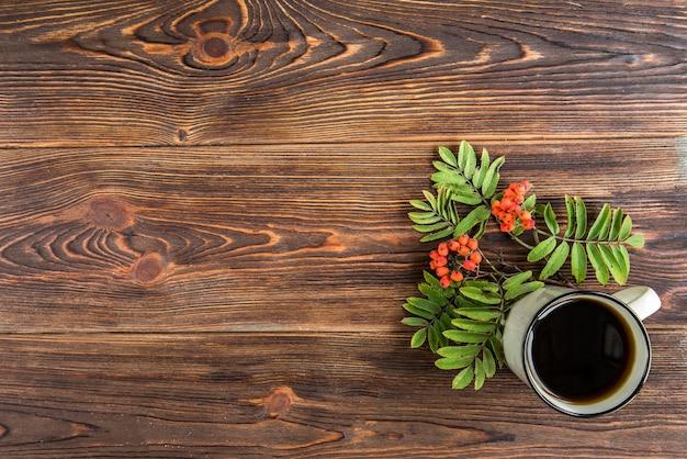 ティーカップとナナカマドの木製の背景。