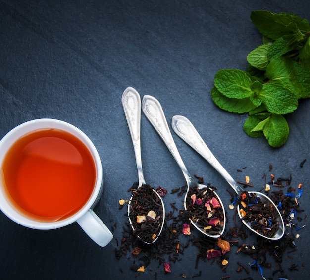 Tea cup and assortment of dry tea in spoons