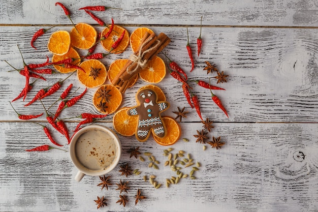 Tea cup, dried oranges, cinnamon sticks and anise, top view