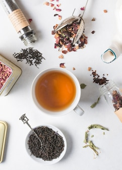 Tea cup is surrounded with different type of dried herbs on white backdrop