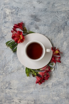 Tea cup on marble table with floral arrangements