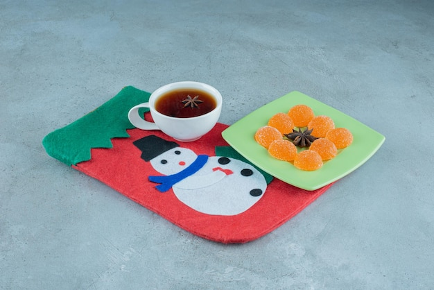 Tea cup and marmelade platter on a christmas sock on marble.