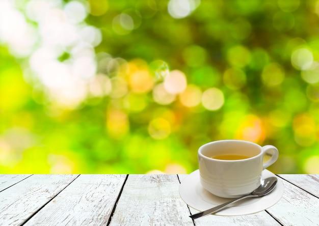 Чашка чая на деревянном столе с абстрактным зеленым летним фоном боке