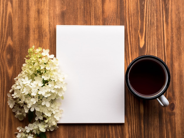 Tea cup, open notepad with a clean white page and white flower of hydrangea