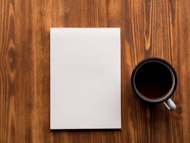 Tea cup and open notepad with a clean white page on wooden table, top view