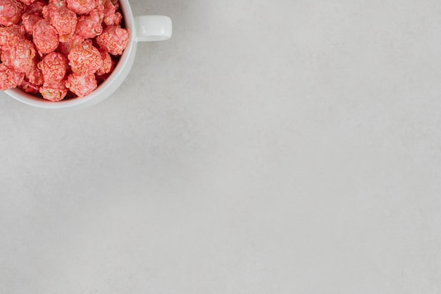 Tea cup overflowing with red, flavored popcorn on marble table.