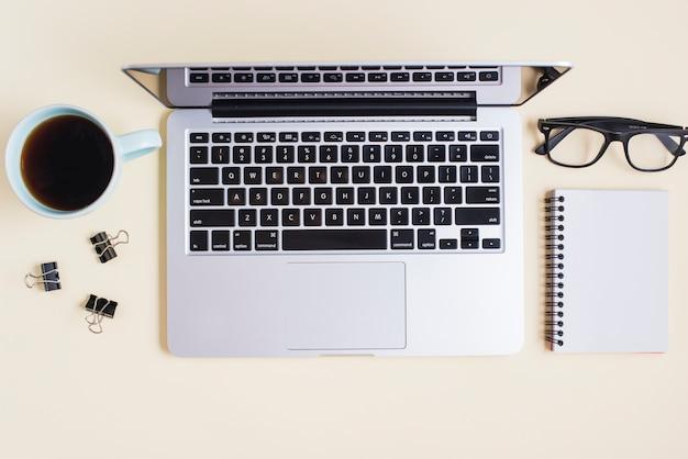 Чайная чашка; скрепки; очки; ноутбук и спиральная тетрадь на бежевом фоне