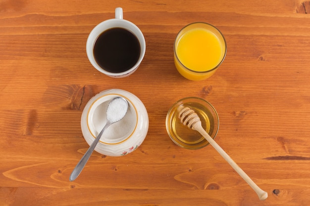 Tea cup; powdered milk; orange juice and honey on wooden desk