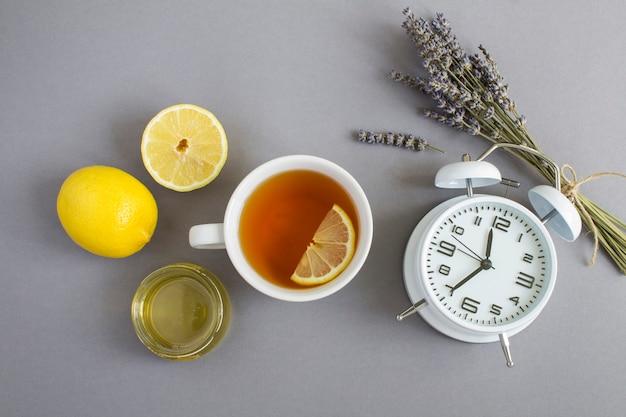 회색 배경에 찻잔, 흰색 알람 시계, 마른 라벤더, 레몬, 꿀. 공간을 복사합니다. 불면증에 대한 약초.