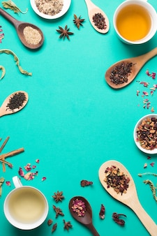 Tea cup with herbal and spices on turquoise background with copy space for writing the text