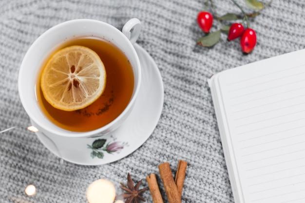 Чайная чашка с лимоном рядом с блокнотом на пледе