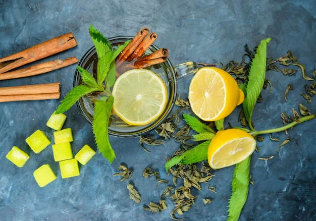 Tea in a cup with lemon, mint, cinnamon sticks, sugar cubes top view on a blue surface
