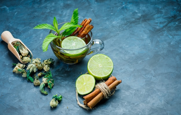 Tea in cup with mint, cinnamon, dried herbs, lime on grungy blue surface, high angle view.