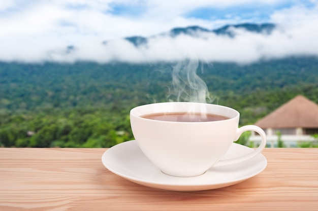 Tea cup with organic tea leaf on the wooden table and tea plantations. mountain jungle background