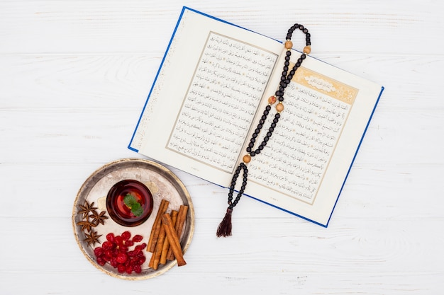 Tea cup with quran and beads on table