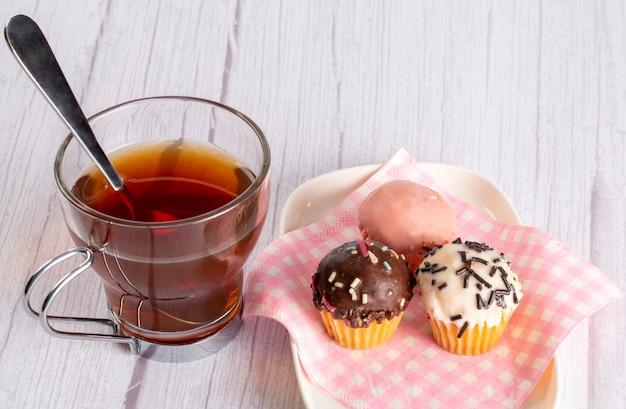 다양한 색상과 맛의 미니 컵 케이크와 함께 나무 테이블에 스푼이 달린 차 컵
