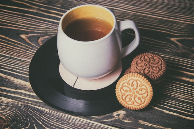 Tea in cup with sweet cake on vinyl records