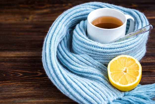 Tea cup with thermometer, blue scarf and lemon on wooden surface. flu season, disease.