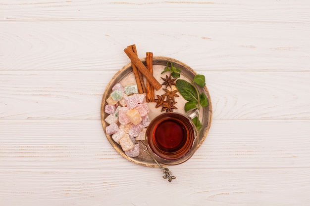 Tea cup with turkish delight and cinnamon on plate