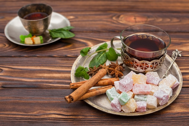 Tea cup with turkish delight on wooden table
