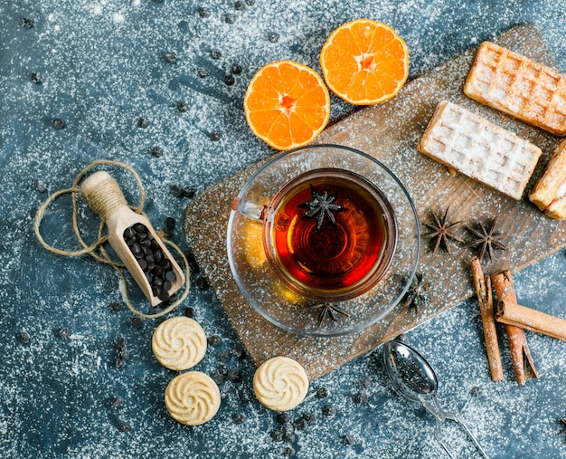 Tea in a cup with waffle, biscuit, spices, choco chips, strainer, orange flat lay on blue and cutting board