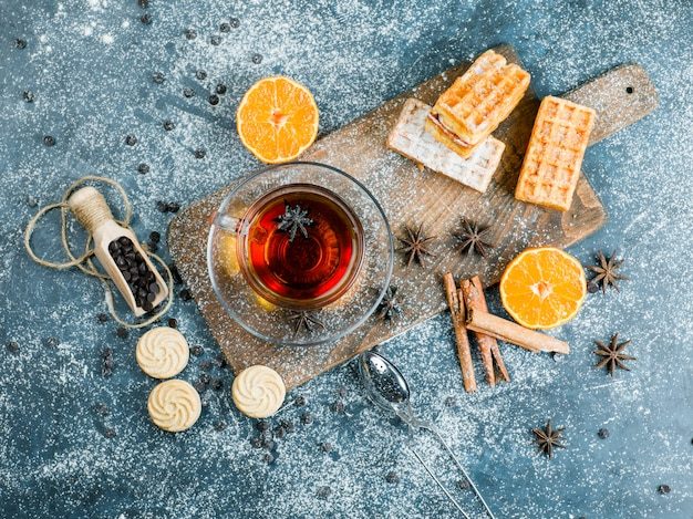 Tea in a cup with waffle, biscuit, spices, choco chips, strainer, orange top view on blue and cutting board