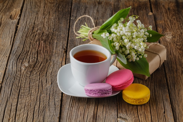 Tea cup with white flower decoration on wooden table