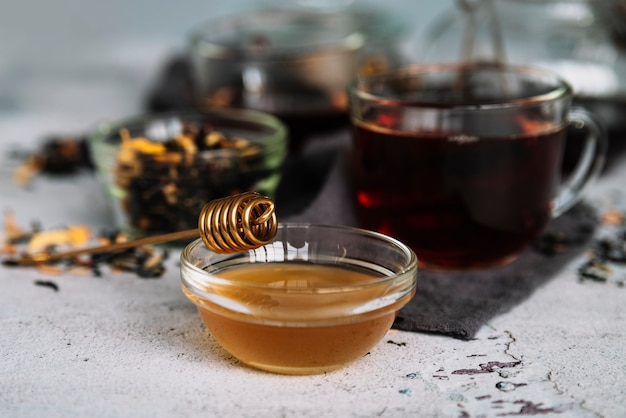 Tea in cups and delicious organic honey