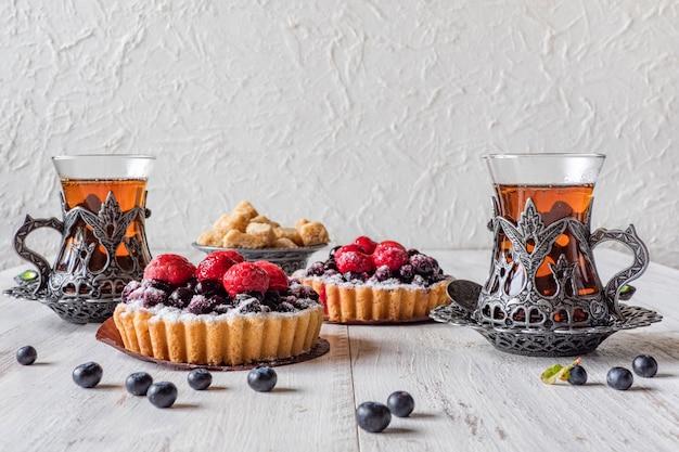 ティーカップ、タルトケーキお菓子、新鮮なラズベリーと白い木製の背景にブルーベリー。
