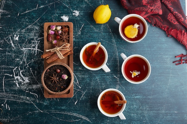 Tea cups with herbs and spices, top view.