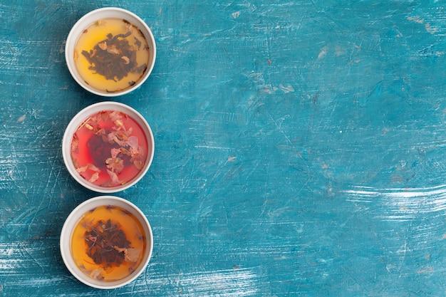 Чай . различные виды сухого чая в керамических мисках и чашках ароматного чая