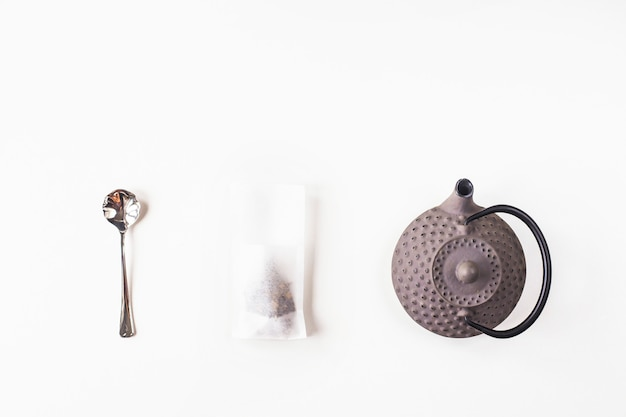 Tea in a disposable filter bag for brewing next to a gray cast iron kettle and a spoon