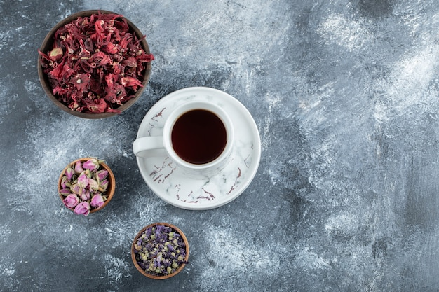 Tea and dried flowers on marble table.