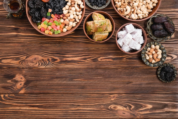Чай; сухофрукты смешанные; орехи; лукум и пахлава на глиняной и металлической миске на деревянном столе