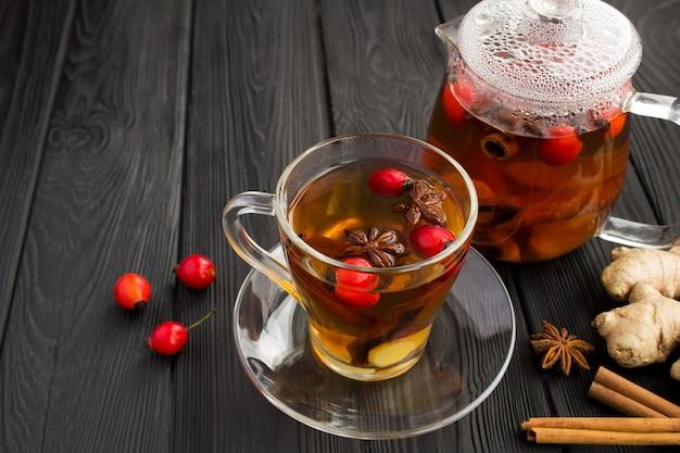 Чайный напиток с шиповником, имбирем и специями в стеклянной чашке на черном