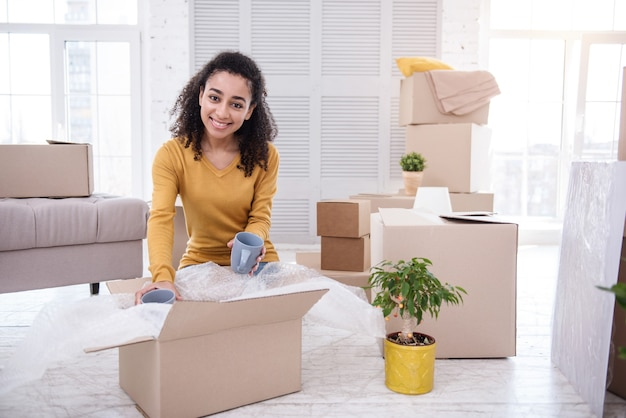 Tea drinker. charming young woman putting tea cups into the box and smiling at the camera while packing her belongings before moving out