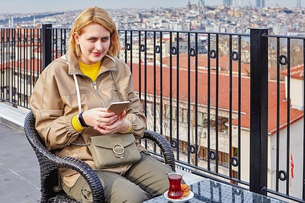 이스탄불의 도시 경관을 배경으로 차를 마시고 스마트폰을 사용하여 친구들과 온라인 커뮤니케이션을 하는 젊은 여성이 인터넷에서 문자를 보내고 있습니다.